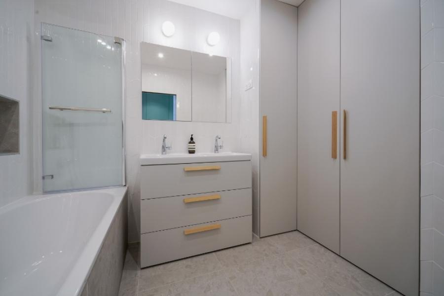 Agencement complet d'une salle de bain en gris clair avec coin buanderie